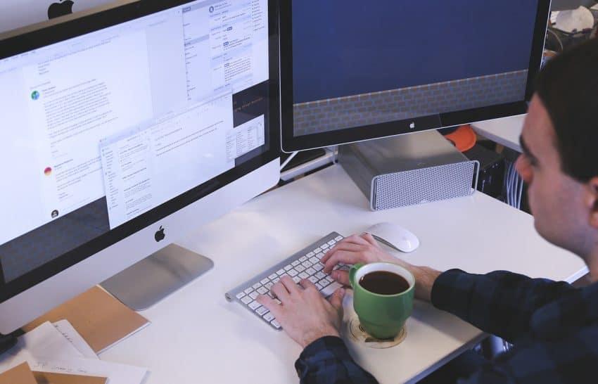 Homem digita texto em um computador.